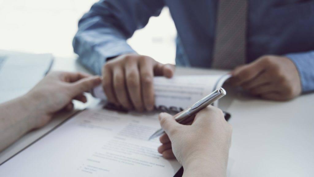 rescisão contratual - pessoa segurando uma caneta para assinar um contrato