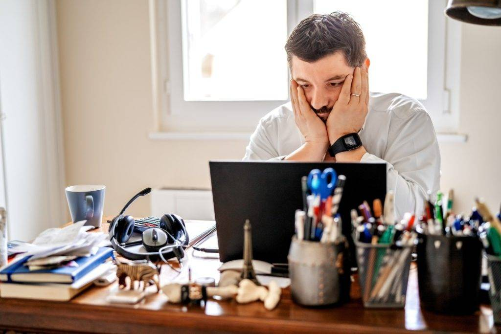 horas extras no home office - homem trabalhando em casa frustrado